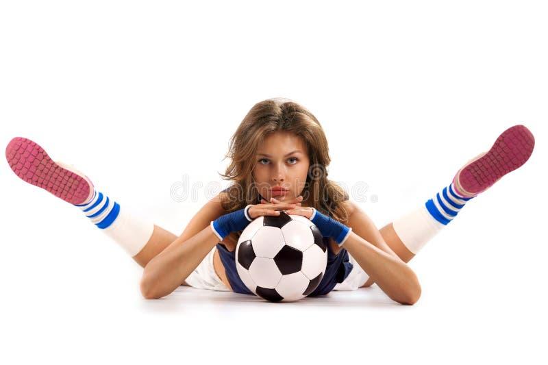 Reizvolles Mädchen mit Fußballkugel stockfoto