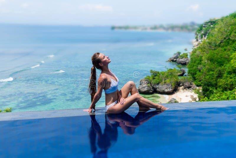 Reizvolles Mädchen Schöne Frau vorbildliche Damenbikiniunterwäsche sitzen Rand des Wasserschwimmenpools auf dem Dach des Luxus-Re lizenzfreie stockfotos