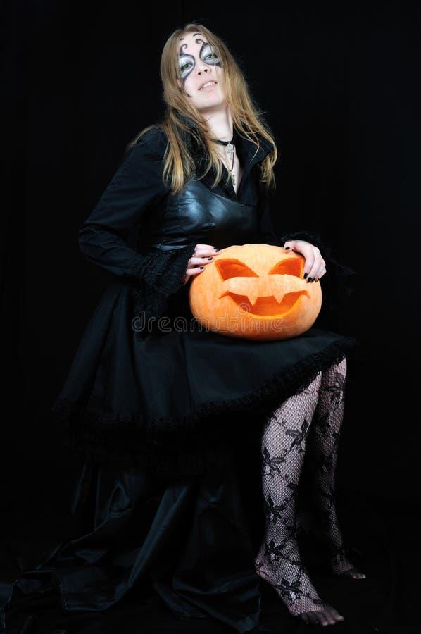 Reizvolles Vampirmädchen mit Halloween-Kürbis stockfotos