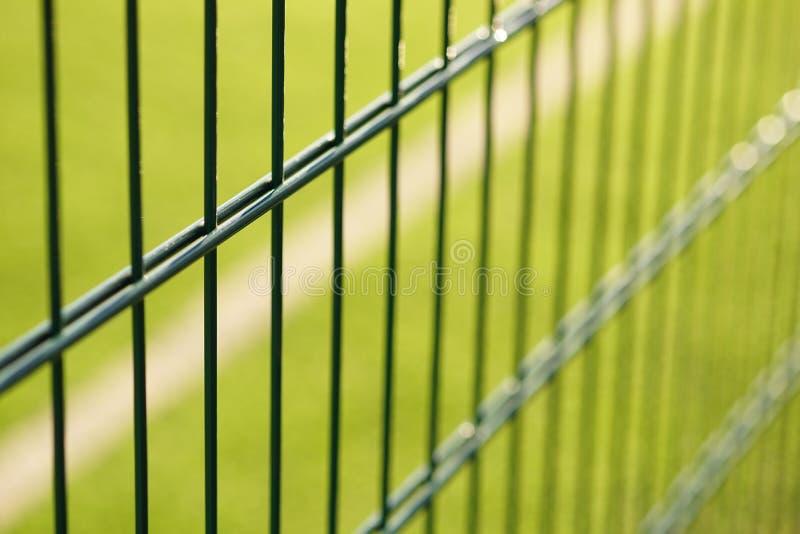Rejilla de la cerca verde en el fondo del campo del césped para jugar a mini-fútbol foto de archivo
