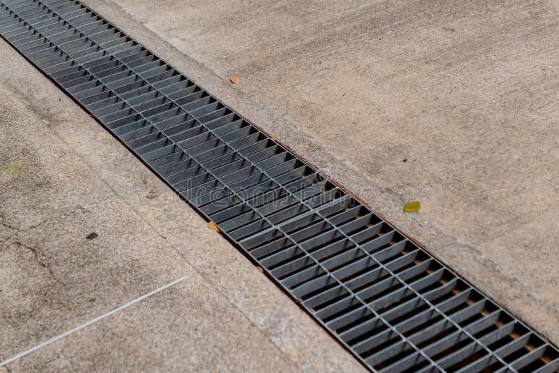 Rejilla del dren de las aguas residuales en el piso del cemento fotos de archivo libres de regalías