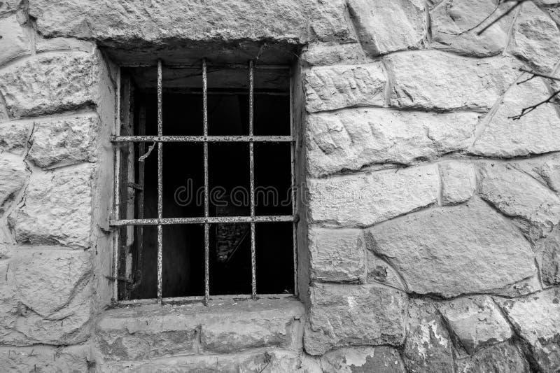 Rejilla del metal en ventana de piedra abandonada vieja de la casa imagen de archivo libre de regalías