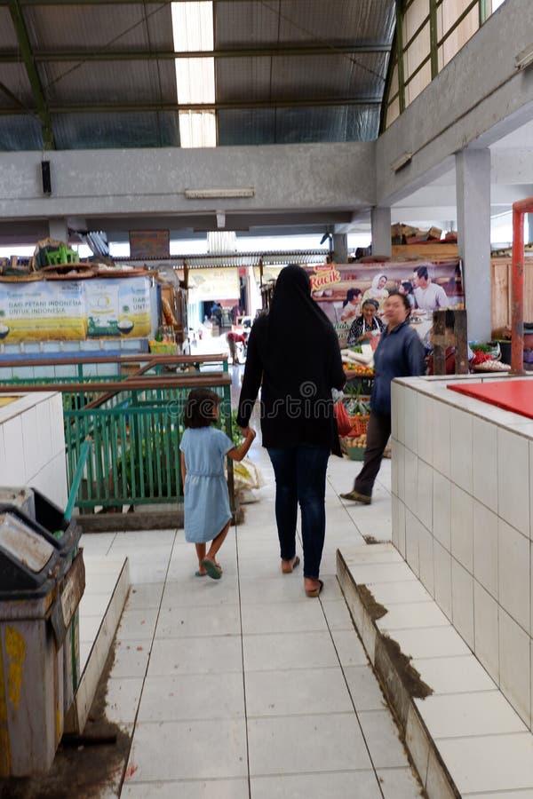 Rejowinangun Magelang, Indonesien - 24 mars 2019: matcha modern och barnet, när shoppa i traditionella marknader royaltyfri bild