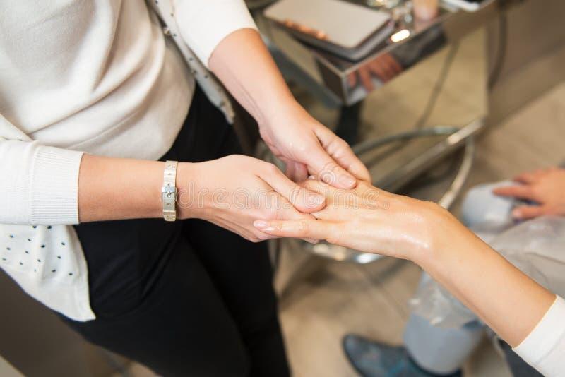 Rejuvenescendo a massagem das mãos da mulher com sal esfregue e loção no salão de beleza dos termas imagem de stock