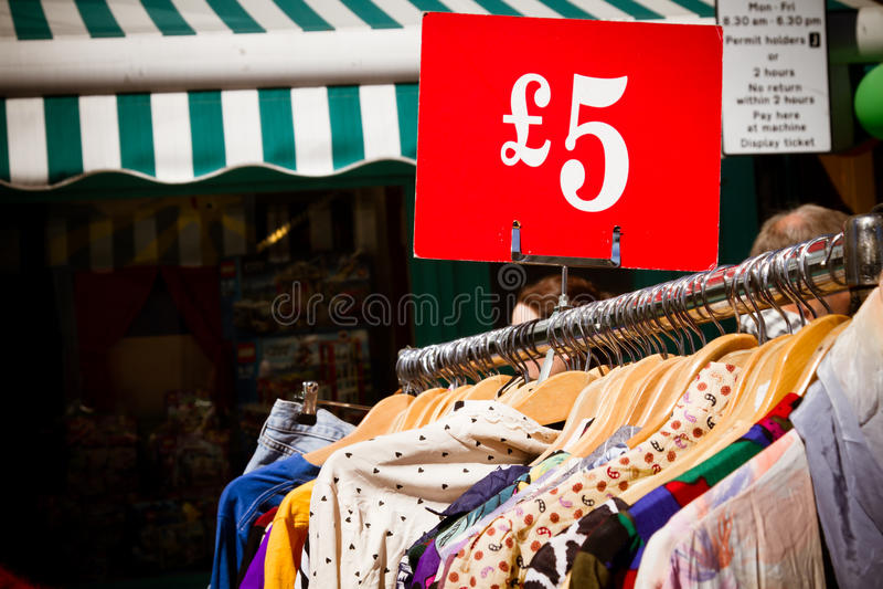 Rek van kleding bij markt stock afbeelding