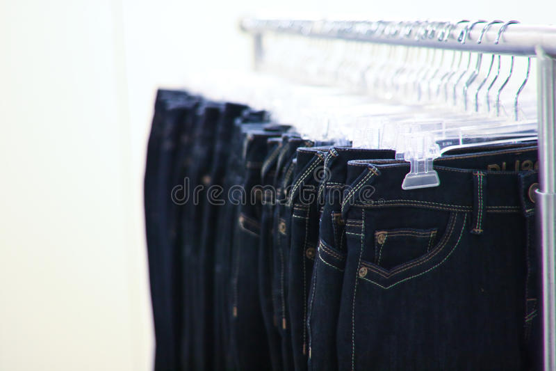 Rekken van Jeans die in een opslag hangen stock fotografie