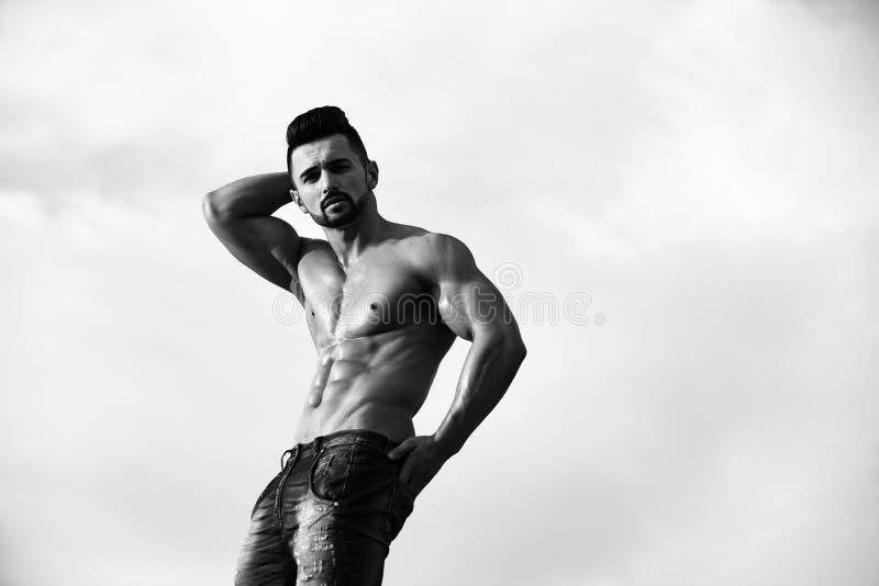 Reklamowi cajgi mężczyzna z mięśniowym ciałem na niebieskim niebie zdjęcie royalty free