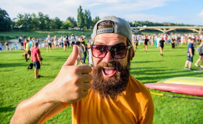 Rekommendera högt den bästa listahipsteren som besöker händelsepicknickfesten eller festival Man som är skäggig framme av folkmas royaltyfri fotografi