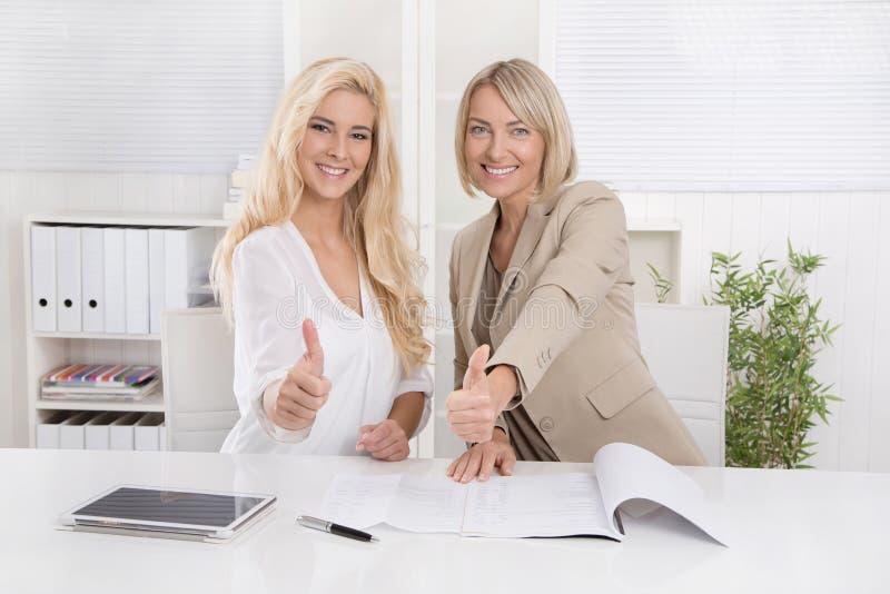 Rekommenderar le blond affärskvinna som två arbetar i ett lag, fina arkivbilder