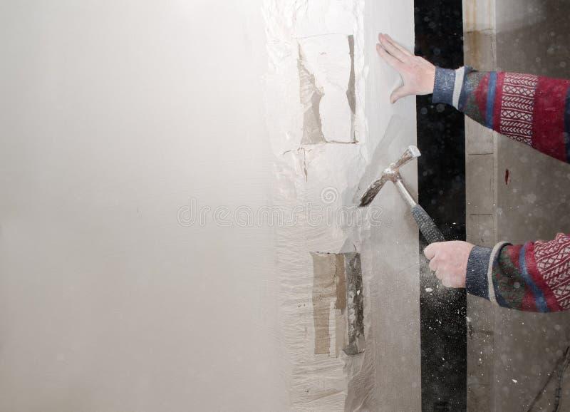 Rekonstruktion und Erneuerung, Handwerker entfernt ein Teil der Wand mit einem Hammer für die Inneninstallation in einer Baustell lizenzfreie stockfotos