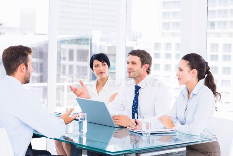 Rekryterare som kontrollerar kandidaten under jobbintervju arkivbild
