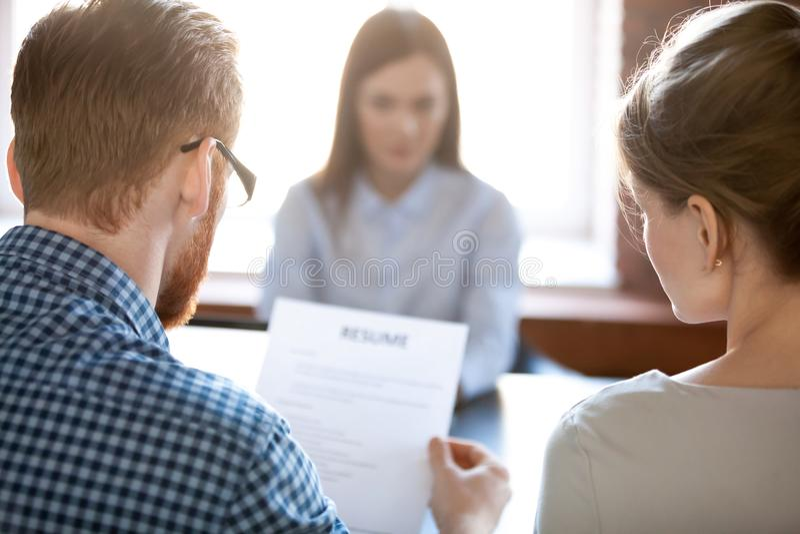 Rekryterare som läser den kvinnliga kandidatmeritförteckningen under intervju fotografering för bildbyråer