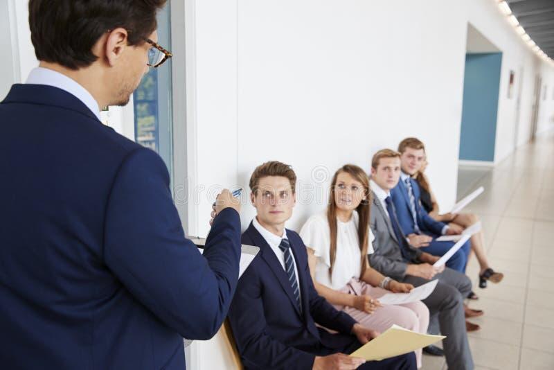 Rekryterare som tilltalar jobbkandidater som väntar på intervjuer arkivbilder