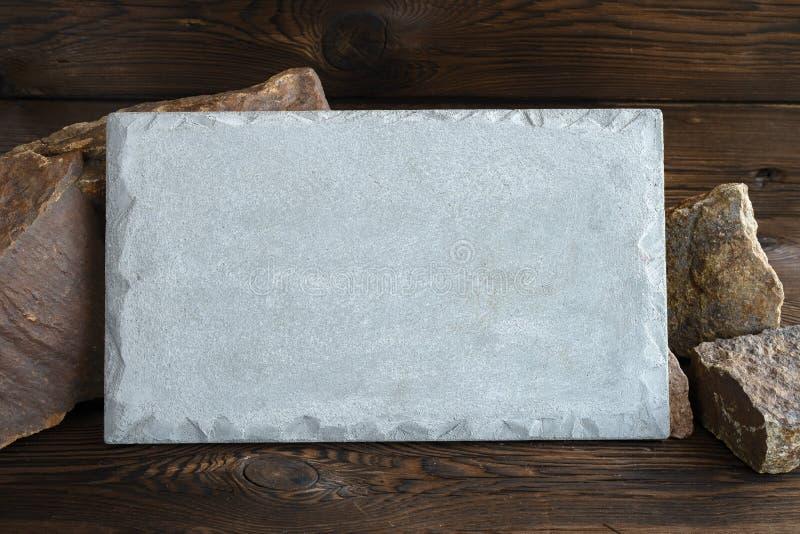 Rektangulär konkret platta på bakgrunden av granitstenar spelrum med lampa royaltyfria foton
