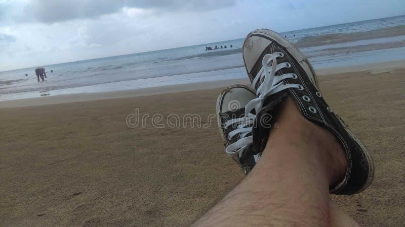 Relájese en la playa con las zapatillas de deportede Conversefoto de archivo libre de regalías