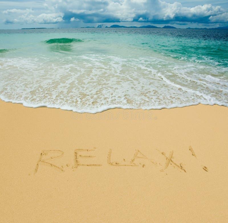 Relájese escrito en una playa tropical arenosa fotos de archivo libres de regalías