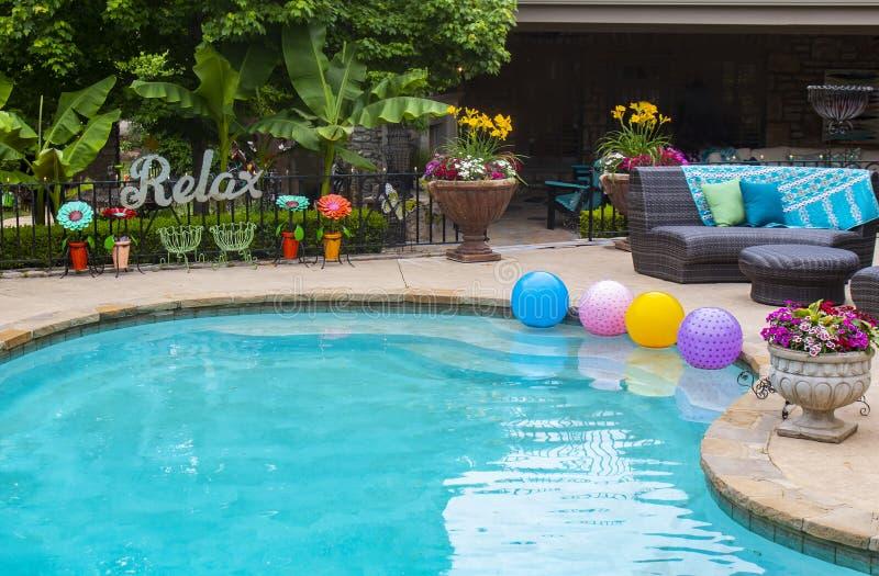 Relájese por la piscina - las flores y las plantas y la decoración por la piscina con un grande RELAJAN la muestra del metal en l imagen de archivo