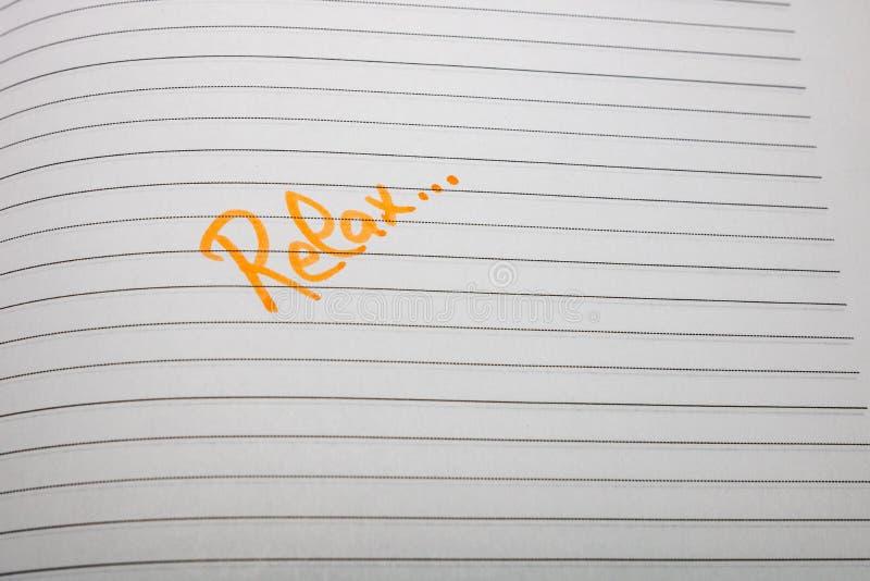 Relájese y escriba a mano en la página de la agenda de la oficina Copiar espacio imágenes de archivo libres de regalías