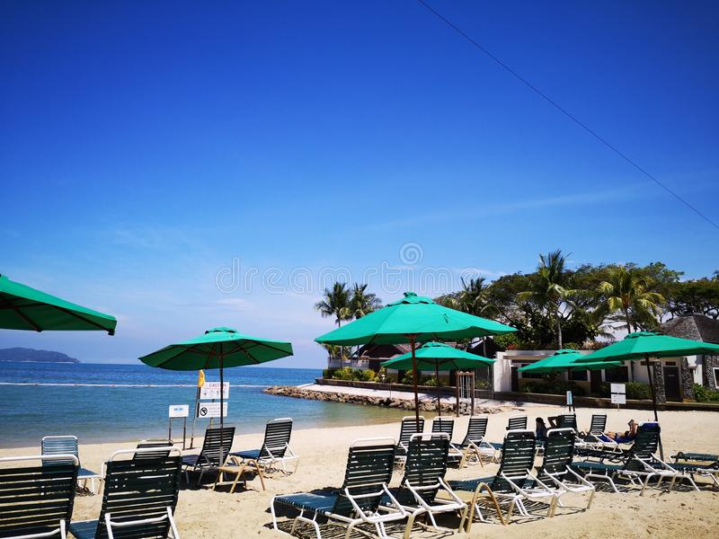 Relájese y goce en la playa con las sillas perezosas en la playa y el cielo azul hermoso arriba imágenes de archivo libres de regalías