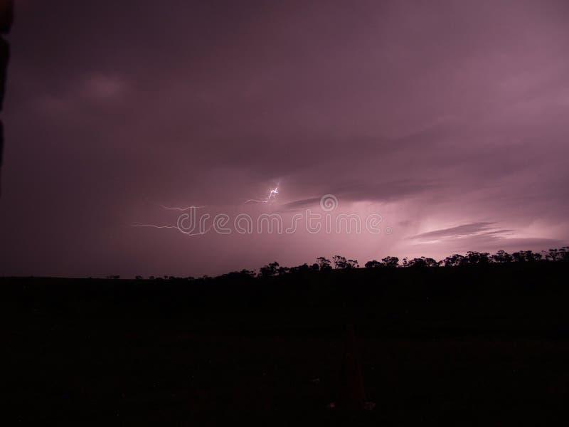 Relámpago en la noche - cielo púrpura imagen de archivo