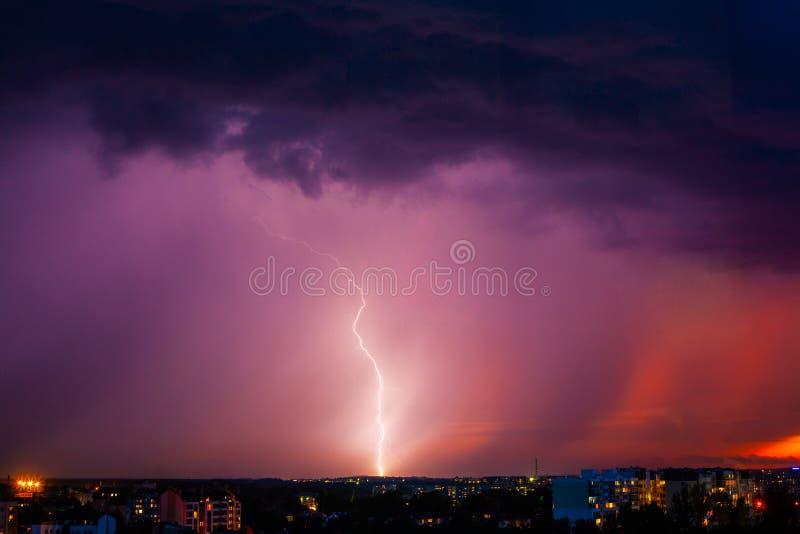 Relâmpago atinge tempestade sobre a luz roxa da cidade fotografia de stock royalty free
