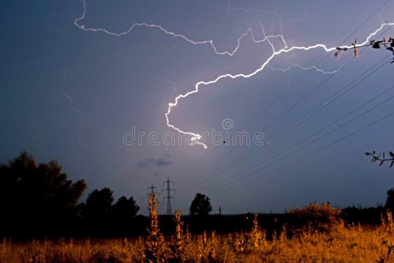 Relâmpago rapidamente em uma noite de verão tormentoso Um campo com polos e fios elétricos imagens de stock royalty free