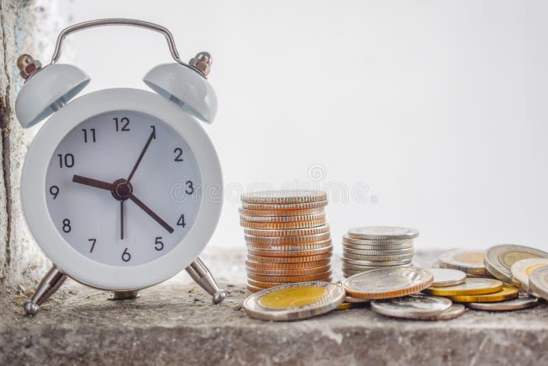 Relógio branco e a moeda tailandesa colocada na borda do patamar junto à parede velha do cimento e a parede rachada - o tempo nun imagem de stock