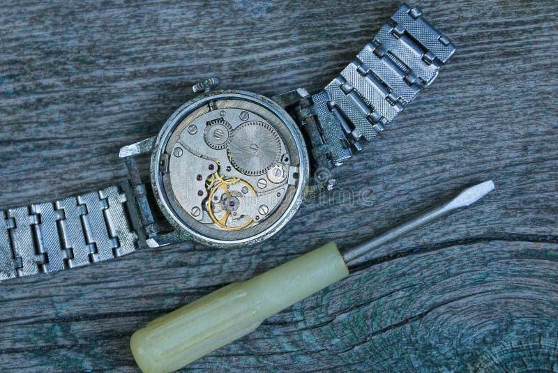 Relógio cinzento velho com um mecanismo aberto e uma correia do metal com uma chave de fenda imagens de stock