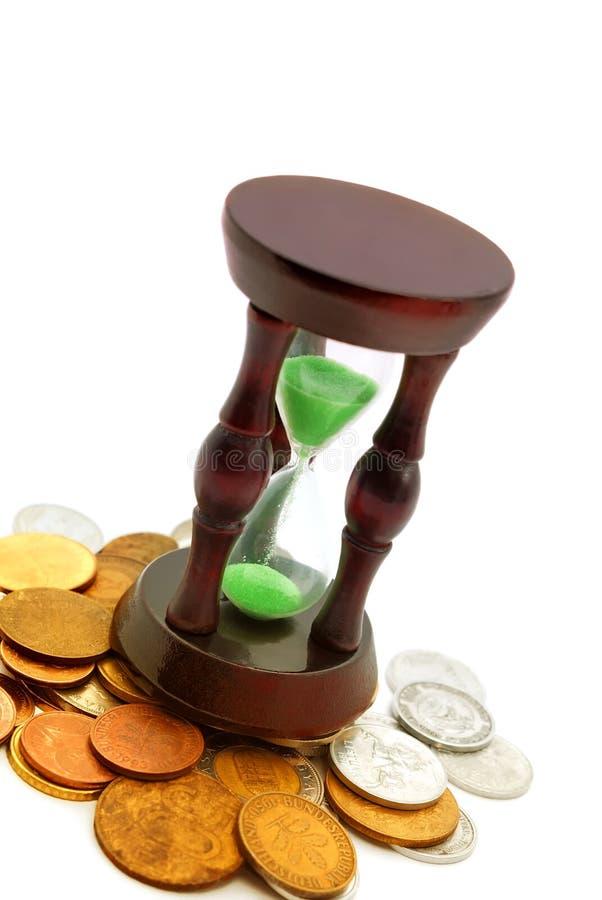Relógio da areia e fundo das moedas fotos de stock