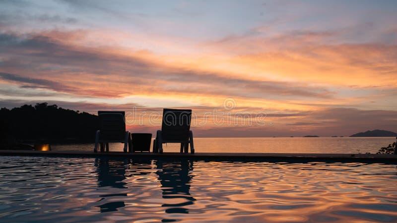 Relógio da cadeira de praia o por do sol na noite no verão em Tailândia imagens de stock royalty free