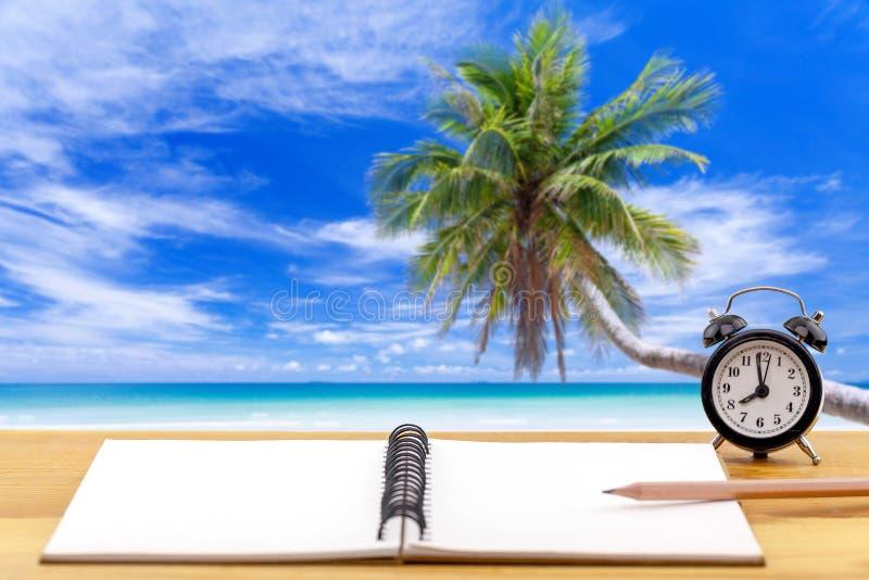 Relógio de alarme com notebook sobre fundo do mar na praia tropical e mar azul imagens de stock