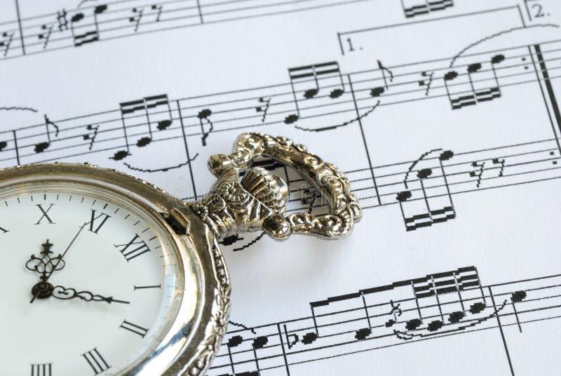Relógio de bolso antigo na folha de música fotos de stock