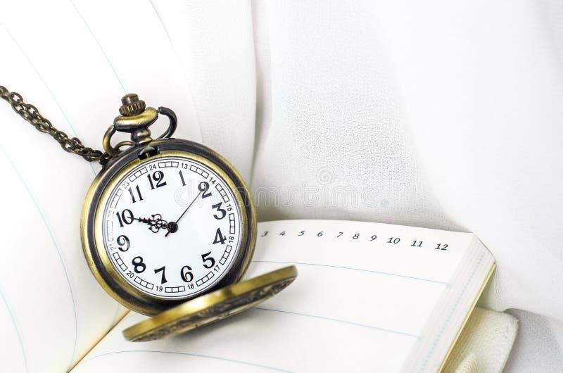 Relógio de bolso do vintage com o caderno no fundo branco da tela fotos de stock royalty free