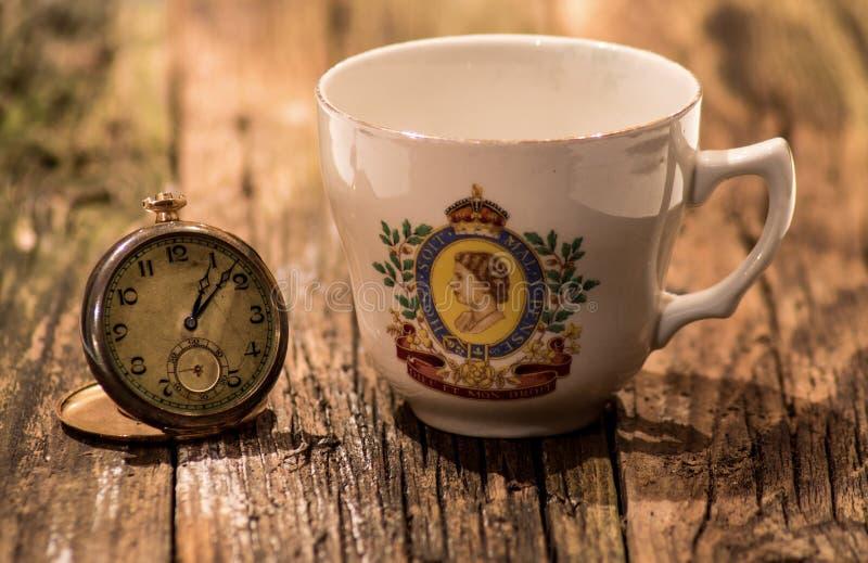 Relógio de bolso do vintage e copo de chá comemorativo imagens de stock