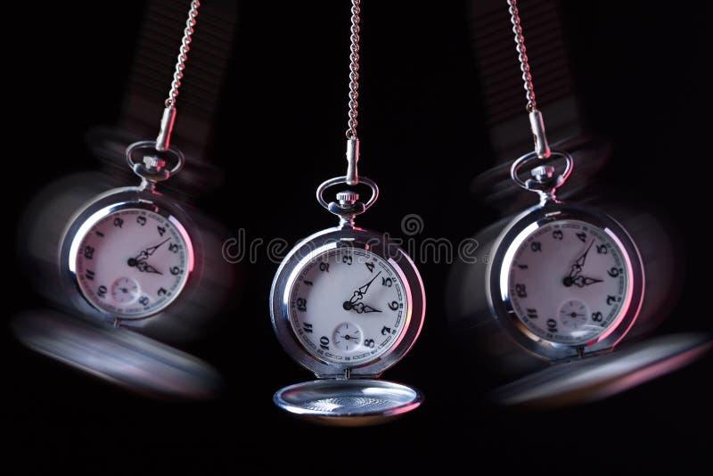 Relógio de bolso que balança em uma corrente para hipnotizar fotos de stock royalty free