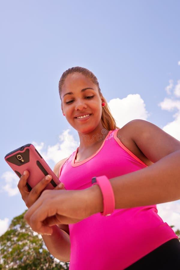 Relógio de conexão Fitwatch da aptidão da jovem mulher com telefone fotografia de stock royalty free