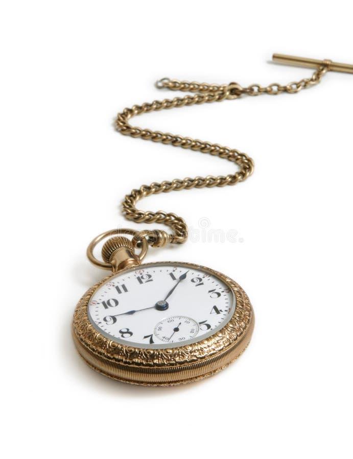 Relógio de ouro do vintage com a corrente que encontra-se no fundo branco imagem de stock
