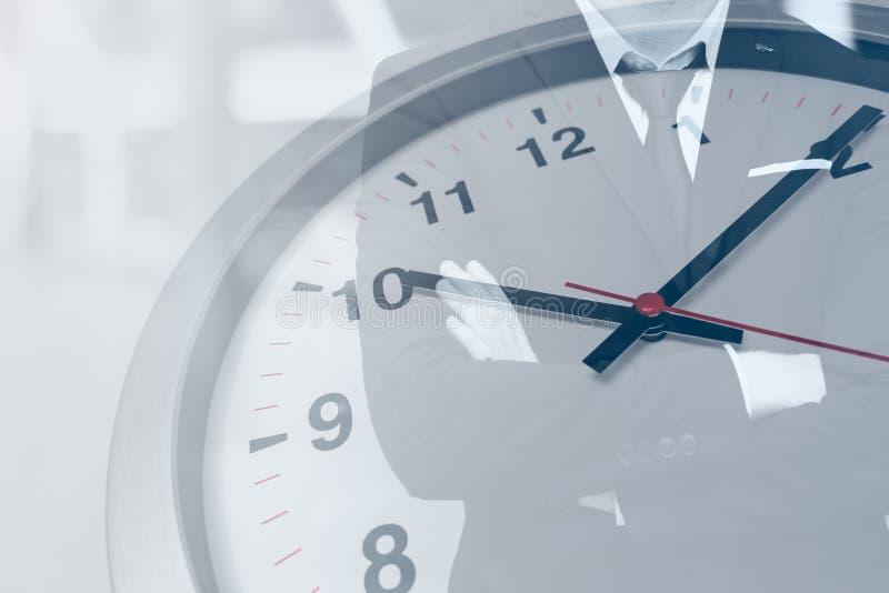 Relógio de ponto com o homem de negócio por horários laborais foto de stock