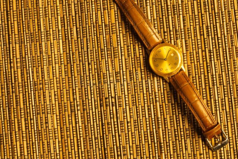Relógio de pulso dourado do vintage com a correia de couro no fundo de bambu foto de stock royalty free