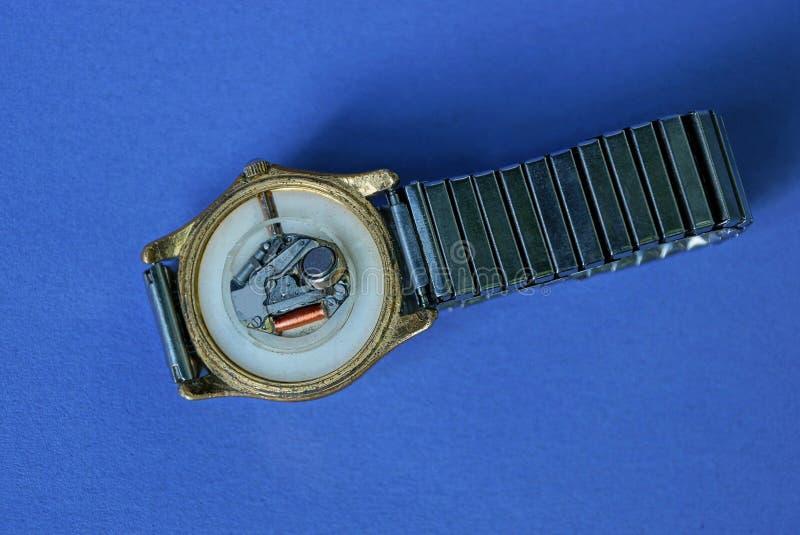 Relógio de pulso eletrônico com um mecanismo aberto e uma correia em uma tabela azul fotografia de stock