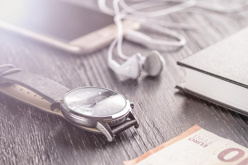 Relógio de pulso, telefone celular com fones de ouvido e bloco de notas no desktop escuro velho do escritório Está próximo a euro fotografia de stock