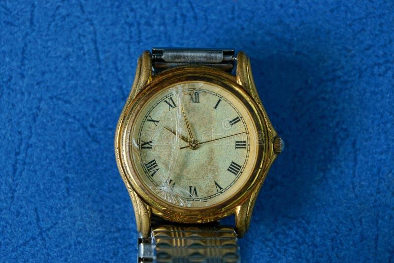 Relógio de pulso velho amarelo com vidro quebrado fotografia de stock royalty free