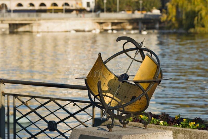 Relógio de sol em um cais ao longo do lago de Genebra foto de stock