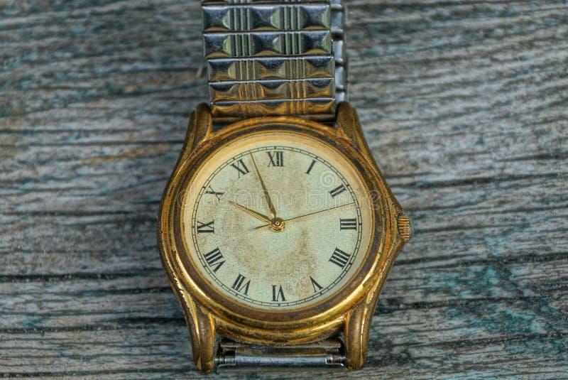 relógio gasto velho amarelo com uma correia do metal em uma tabela cinzenta fotos de stock royalty free