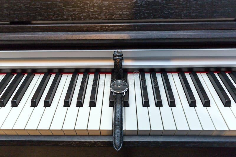Relógio no teclado de piano Conceito do tempo e da música foto de stock royalty free