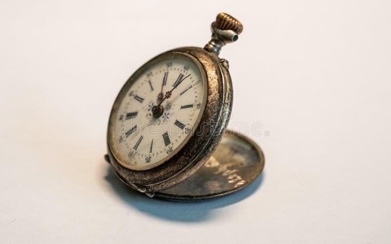 relógio pequeno muito velho antigo do relógio de bolso do vintage oxidado no fundo branco fotografia de stock royalty free