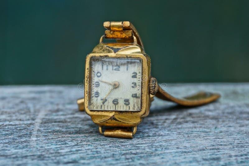 Relógios de pulso amarelos gastos velhos em uma tabela cinzenta fotos de stock