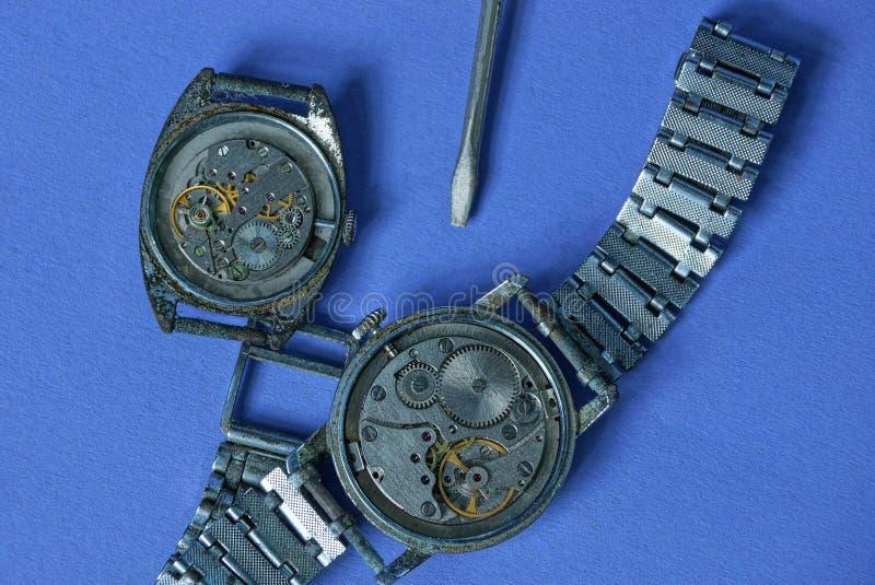 relógios velhos com um mecanismo aberto e uma chave de fenda em uma tabela azul fotos de stock