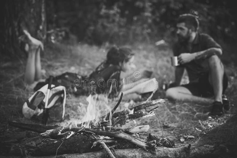 Relações entre mulheres e homens na natureza Chama da lenha na queimadura da fogueira e em pares borrados fotografia de stock