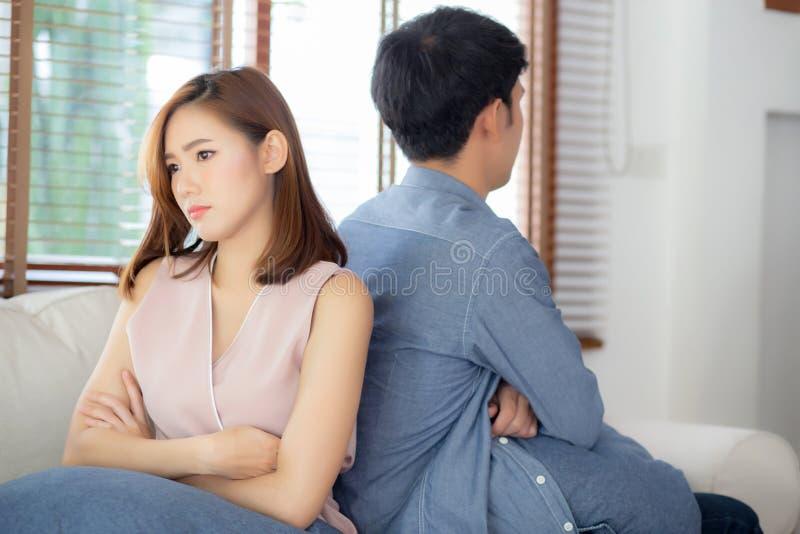 Relación de los pares asiáticos jovenes que tienen problema en el sofá en la sala de estar en casa imágenes de archivo libres de regalías